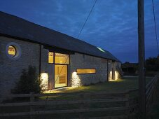 Renovated farmhouse at dusk with illuminated windows