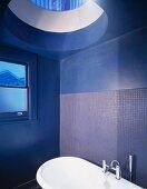 Blue-painted bathroom with bathtub beneath glass cupola