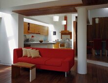 Side table in front of red sofa with open-plan kitchen in background