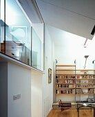 Wohnraum mit modernen Wandregalen und verglastem Schlafraum auf Galerie