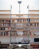 Teilweise sichtbarer Couchtisch mit Glasplatte vor modernem Bücherregal