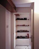 Blick durch offenstehende Tür auf eingebautes Regal mit Schuhen