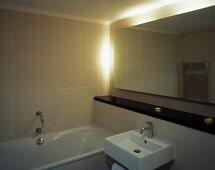 Badezimmerecke im minimalistischen Stil mit hinterleuchtetem Wandspiegel