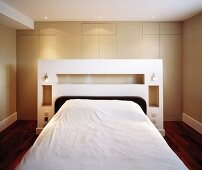 Double bed with white shelf at the head