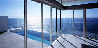 View of swimming pool and sea through glass wall