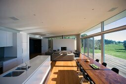 Open-plan living space with glass wall leading to terrace