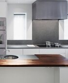 Kitchen island with wood and stone work surface in front of kitchen unit