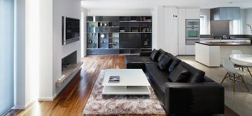 Black leather couch in open-plan, modern living space