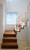 Modern stairwell with square spiral wooden staircase and stainless steel balustrade