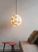Designer lamp hanging above stool next to sofa