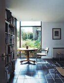 Round table and chair in study with bookcase