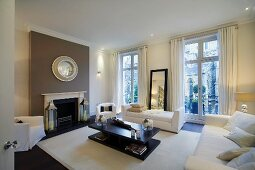 White, modern upholstered furniture and black coffee table in old building in London