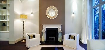 Covered armchairs and retro standard lamp in front of open fireplace