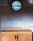 Wall clock and fifties cabinet against unrendered, concrete block wall