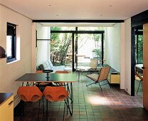 A modern living room with 1950s-style furniture, brown tiles and view into a bamboo garden