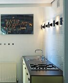 Simple kitchen unit in pastel yellow and grey with modern wall lights and aerial photograph
