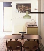 Dining area with wooden shell chairs and industrial-style wall lamp in front of straight-edged kitchen unit