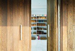 A view though an open wooden door onto a book shelf