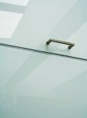 Bracket handle on white cupboard door with frosted glass surface