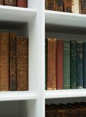 Antiquarian books in white, modern bookcase with tapered edge profiles
