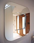 Square mirror with rounded corners reflecting front door