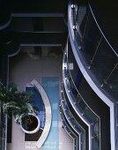 Blick von oben auf Palme und Wasserbecken in offener Erschließungshalle eines Appartementhauses