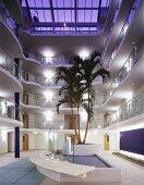 Offen gestaltete Erschließungshalle eines Appartementhauses mit großflächigem Glasdach