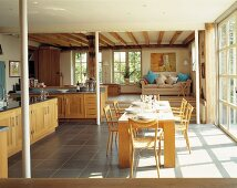Sunny kitchen-dining room with raised living area in young, modern style