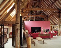 Antique pieces and pink wall with fireplace in old, converted barn