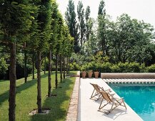 Landscaped garden with wooden deckchairs next to swimming pool