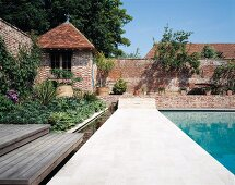 Pool area with summerhouse sheltered by enclosing brick wall