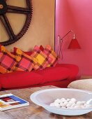 Antique cog above bright pink sofa and bowl of pebbles on antique table