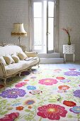 Rug with cheerful, floral pattern on front of Rococo-style sofa in living room
