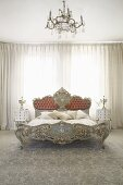 Rococo-style double bed in front of closed curtains in bedroom