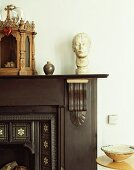 Detail of antique, dark wood mantelpiece with bust