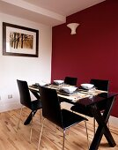 Set dining table with black chairs in front of dark red wall