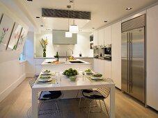 Gedeckter Esstisch in weisser Designerküche