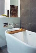 Detail of free-standing bathtub with designer, wall-mounted taps