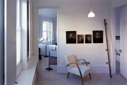 50s armchair in front of ancestral portrait gallery in modern room