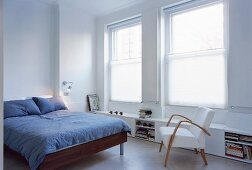 Bed with grey bed linen and 50s armchair in modern bedroom
