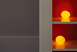 Spherical, yellow lamps on shelves