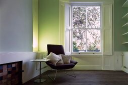 Armchair and side table next to window in minimalist room with classic feel