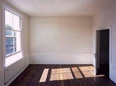 Pattern of light on dark wood floorboards in empty room