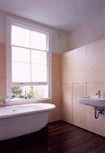 Vintage bathtub in bathroom with modern wooden installation against wall