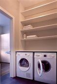 Utility room with two washing machines below shelving