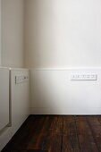 Half-height, white wood panelling with rows of plug sockets above old floorboards