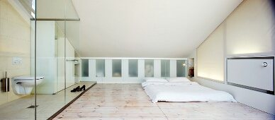 Minimalist bedroom with glazed ensuite bathroom in attic