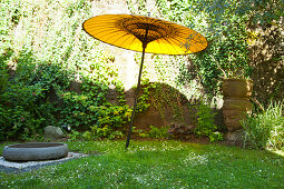 Yellow paper parasol, large stone basin and head of Buddha on lawn