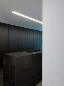 View of dark grey, modern kitchen island and fitted cupboards through doorway