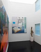 Pictures and sculpture in modern room with skylight